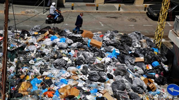 Man walks past masses of rubbish in Beirut street