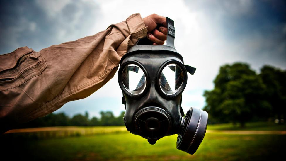Un brazo sostiene una máscara antigas