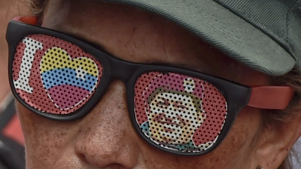 A supporter of Venezuelan President Nicolas Maduro wearing glasses depicting Venezuelan late President Hugo Chavez, attend a rally in Caracas on May 14, 2016.