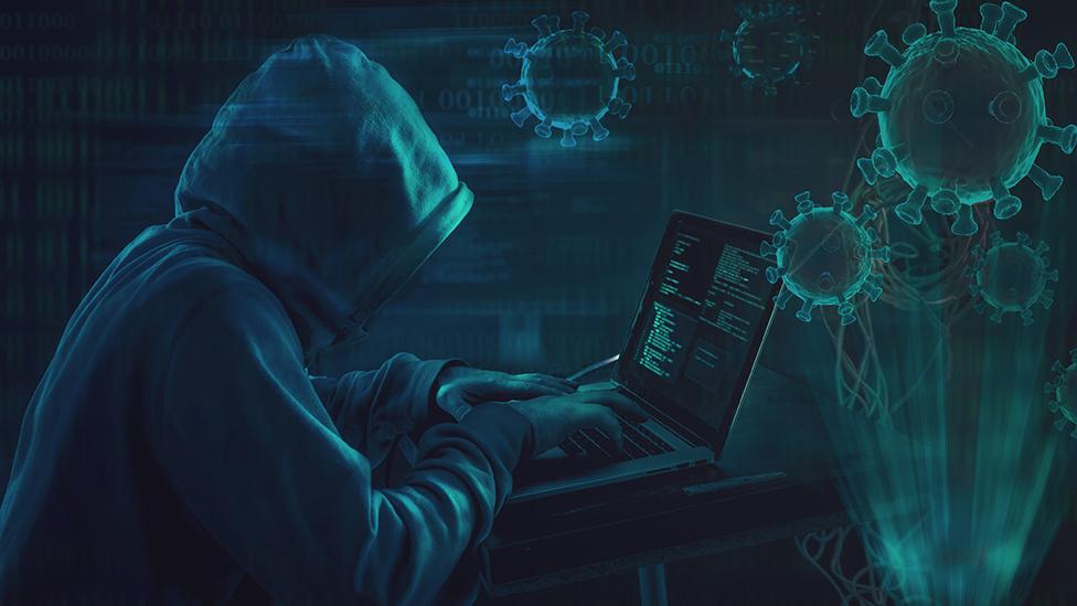 Un hombre con una capucha escribe en su computadora, en medi de imágenes de coronavirus