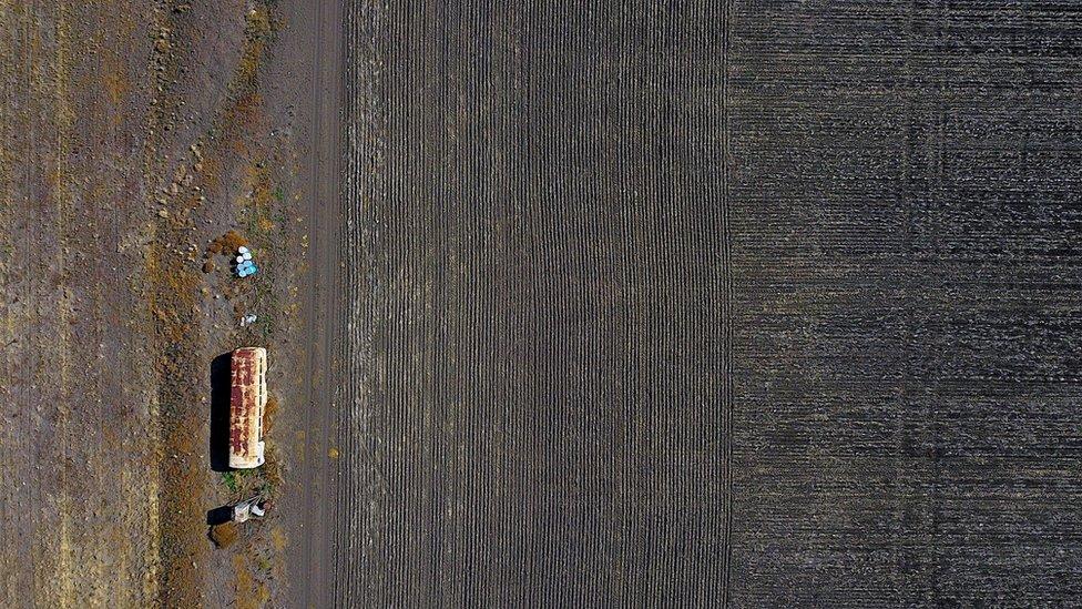 Un viejo autobús utilizado para almacenar equipo agrícola se encuentra en un prado afectado por la sequía al oeste de la ciudad de Gunnedah.