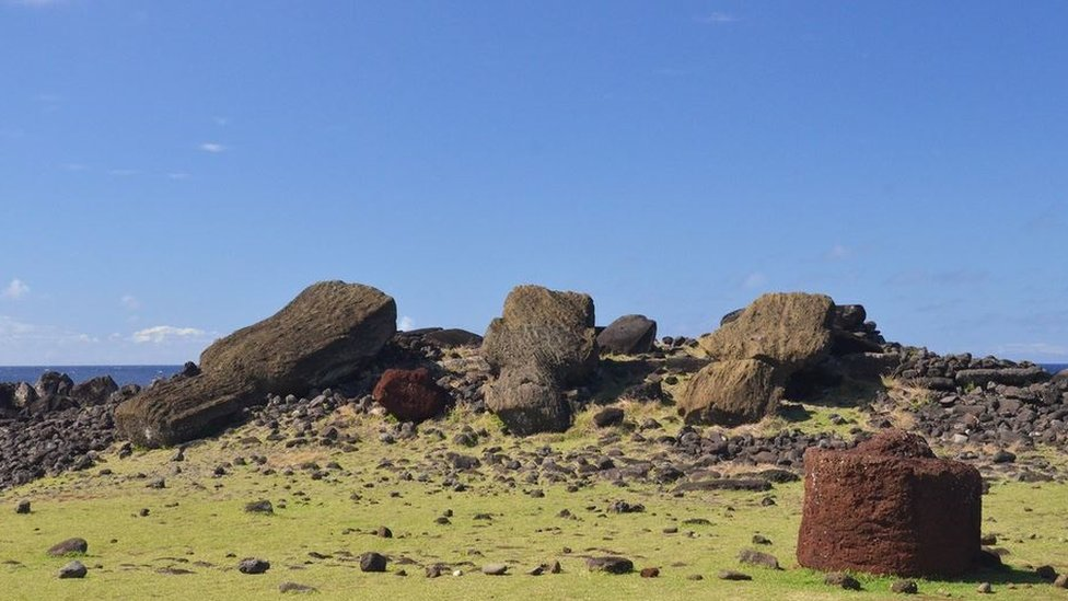 Red scoria pukao hat with tuff rock in background