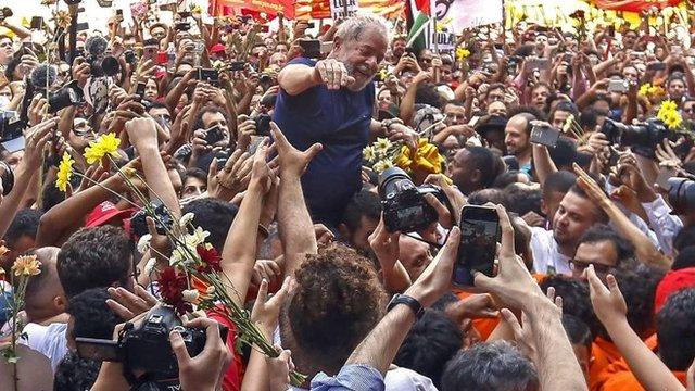 Lula da Silva arropado por cientos de seguidores.