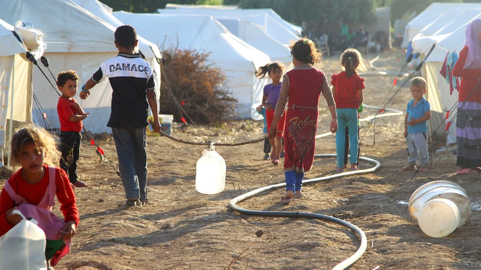 Children walk inside a camp for internally displaced persons near the Syrian-Turkish border in Salqin, Idlib countryside, Syria, in June 2015
