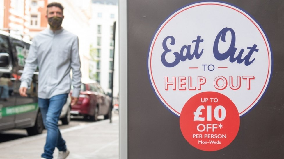 A poster for the Eat Out to Help Out scheme with someone walking in the background