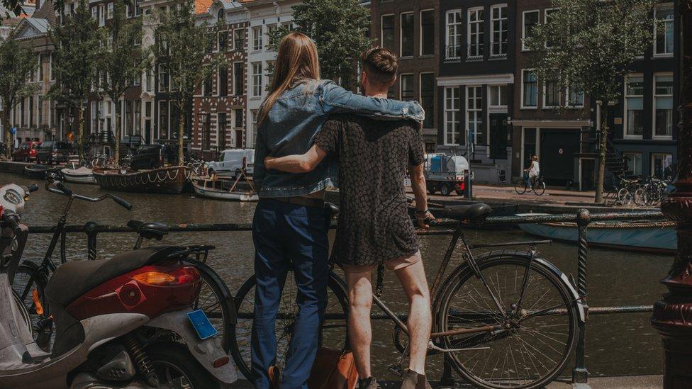Una mujer alta abraza a un hombre frente a un canal en Ámsterdam