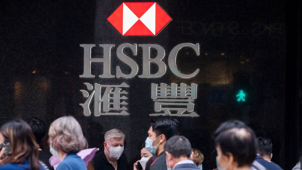 People walking past HSBC sign