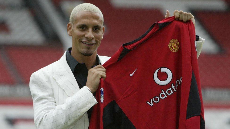 Rio Ferdinand holding up a Manchester Utd shirt