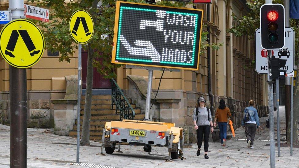 Cartel en el inglés invitando al público a lavarse las manos.