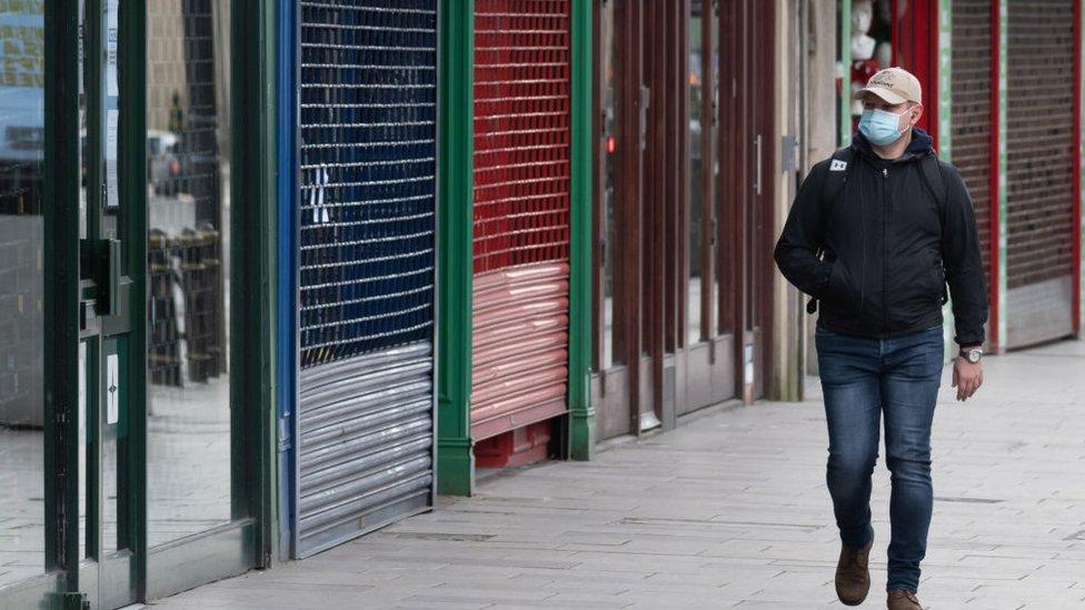 Hombre frente a negocios cerrados