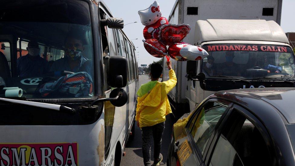 Vendedor de globos en medio del tráfico en Perú.