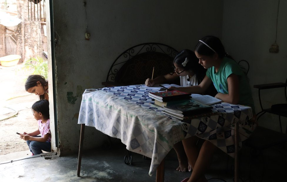 Valeria Torres with one of her students working at the table. Through the open door you can see the dirt courtyard and two younger children waiting.