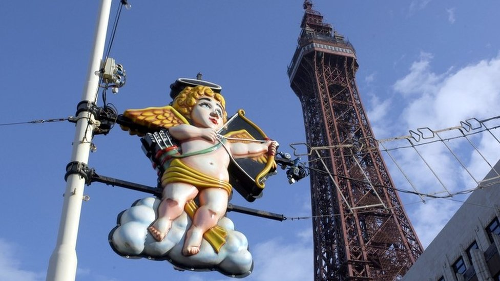 Cupid is seen as a rather gaudy light on the Blackpool Illuminations, with Blackpool Tower in the background