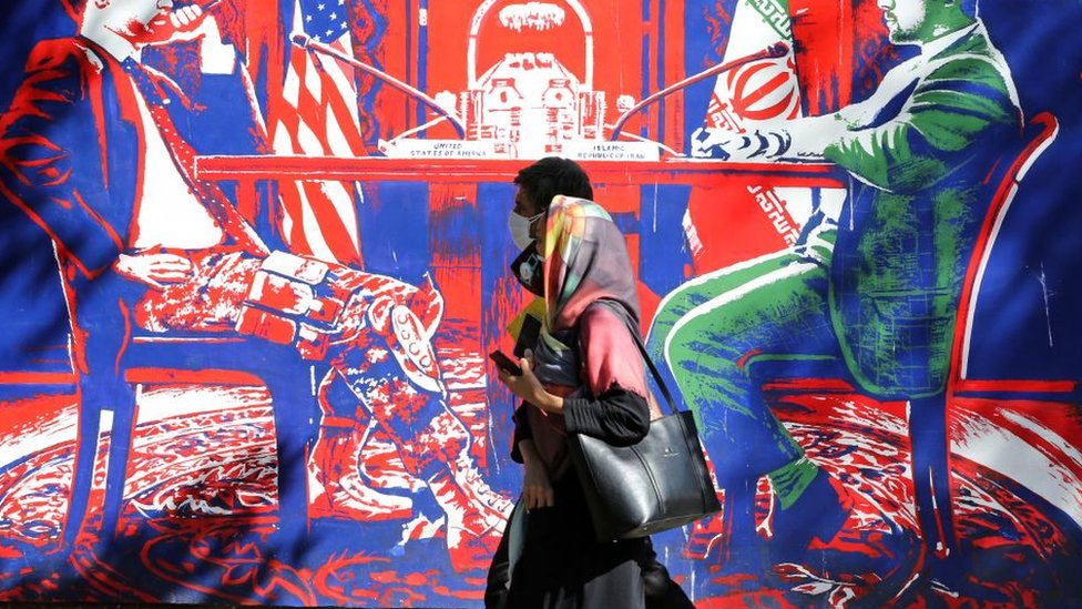 A couple, wearing protective masks amid the COVID-19 pandemic, walks past a mural painted on the outer walls of the former US embassy in the Iranian capital Tehran