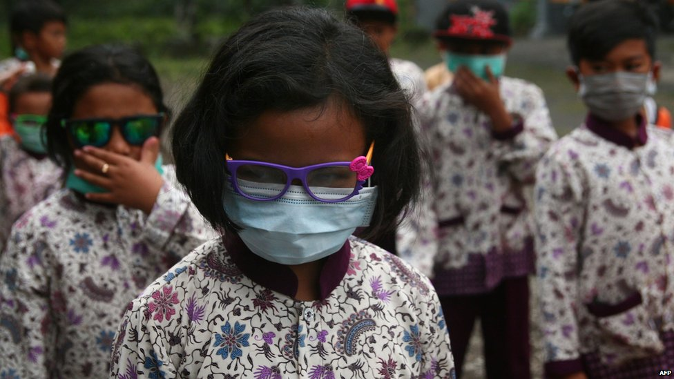Indonesian students wear face masks and glasses to protect them from a volcano eruption
