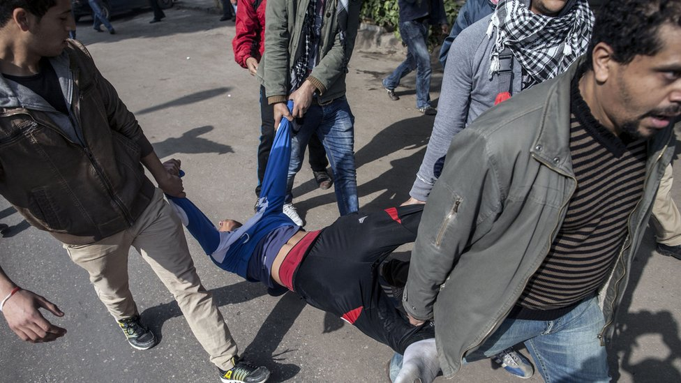 Egyptian anti-government protesters carry a person injured by a rubber bullet fired by police during clashes in Cairo on 25 January 2014