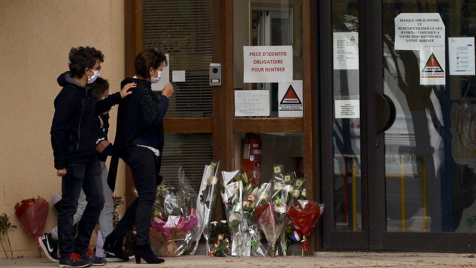تلاميذ وأولياء أمور يضعون الزهور في مكان الحادث