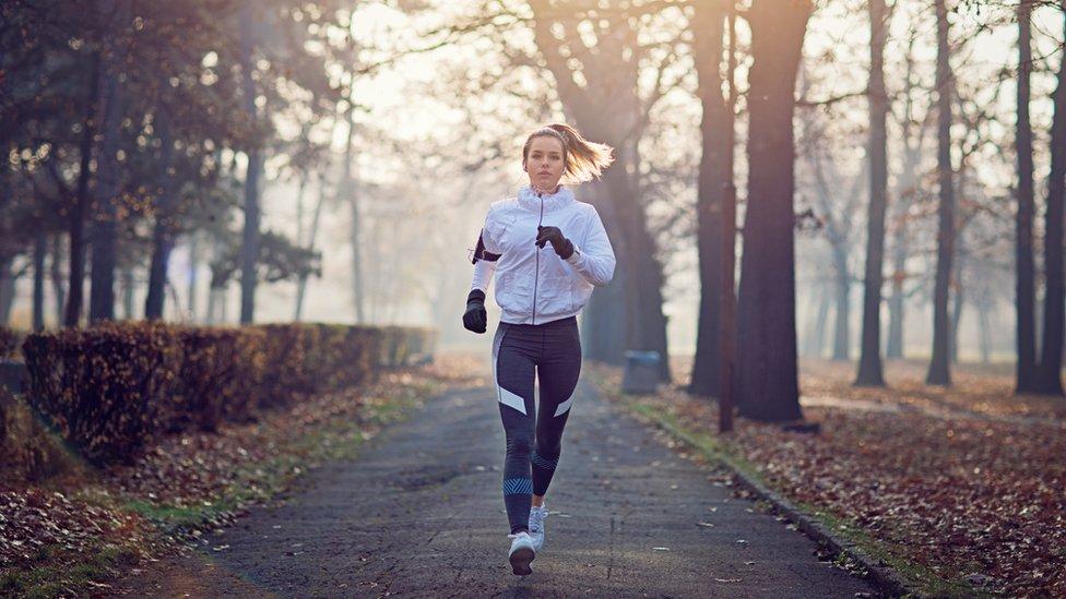 Mujer corriendo en el bosque.