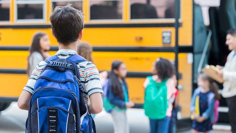 Niño a punto de subir al autobús escolar