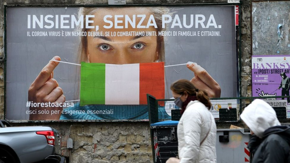 """أشخاص في مدينة نابولي الإيطالية يمشون أمام لوحة ضخمة تظهر امرأة ترتدي قناعاً واقياً بألوان علم البلاد مكتوب عليه """"كلنا معاً من دون خوف"""" في مواجهة فيروس كورونا"""