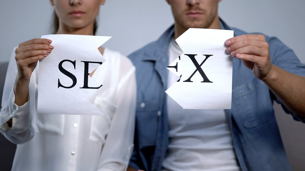 Una pareja rompiendo una hoja con la palabra sexo en inglés