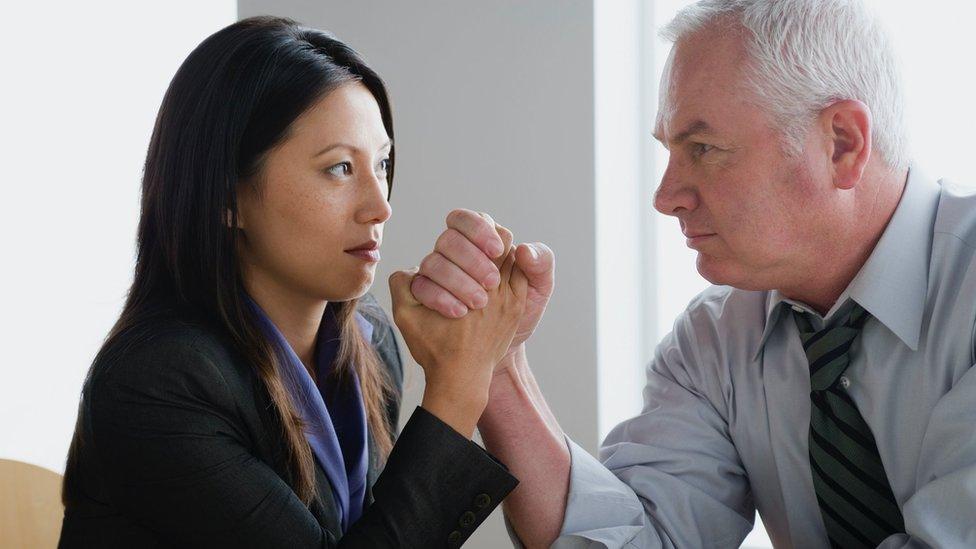 Un bras de fer entre une femme et un homme au bureau