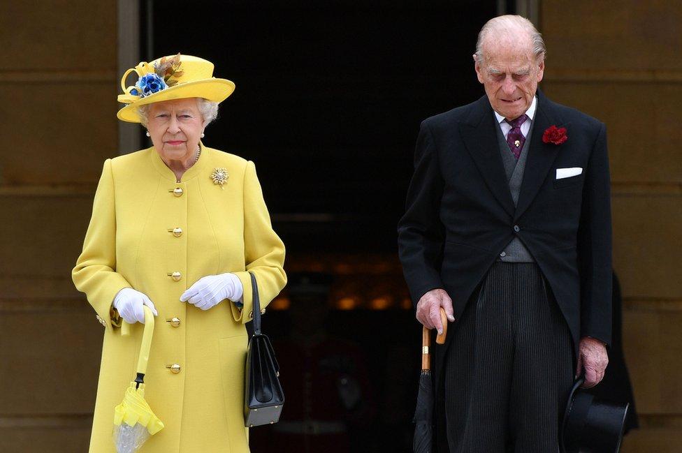 La reina Isabel II y el duque de Edimburgo guardando un minuto de silencio al comienzo de una ceremonia en el jardín del Palacio de Buckingham en Londres, el 23 de mayo de 2017.