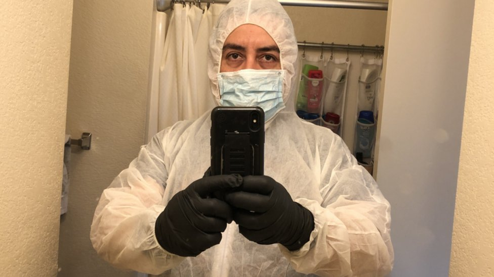 José Zaragoza in his cleaning gear, including a full body coverall, gloves and a mask