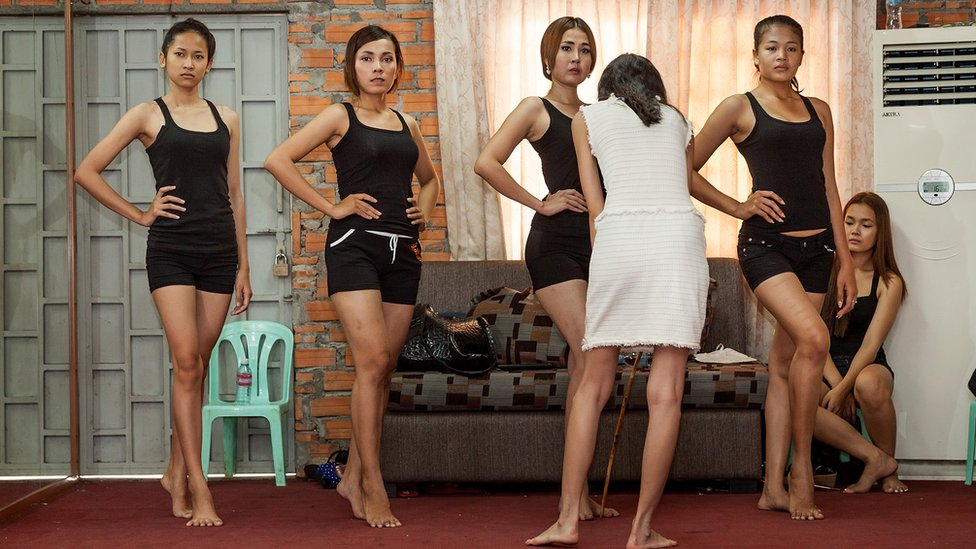 Cambodian models pose in shorts and t-shirts.