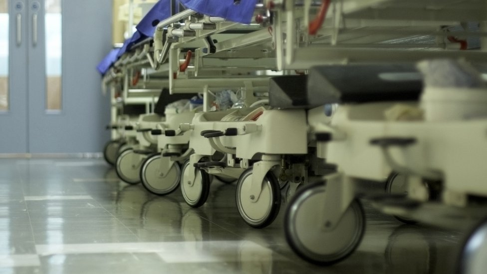 Hospital beds lined up in a corridor