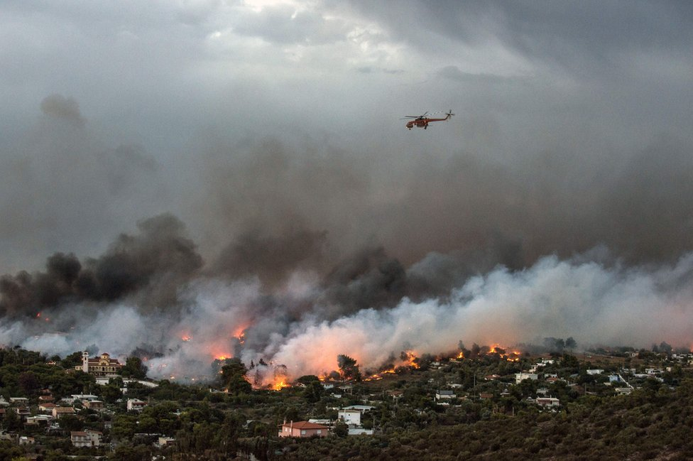A firefighting helicopter flies over a wildfire raging in the town of Rafina