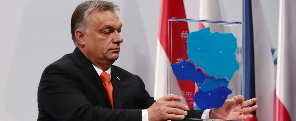 Hungarian Prime Minister Viktor Orban lifts a box depicting the V4 member countries on 21 June