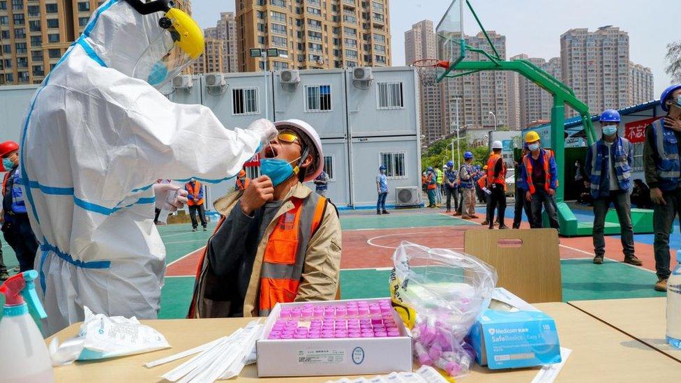 Vuhan'daki Vanda inşaat bölgesinde çalışan göçmen işçilere ise mesai öncesi koronavirüs testi yapılıyor.