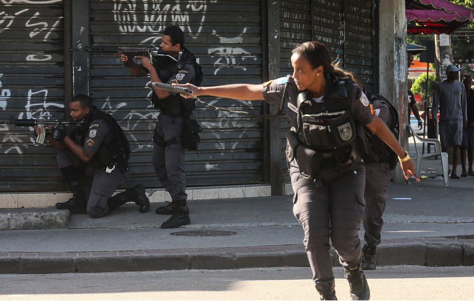 Military Police (PM) officers patrol in the Cidade de Deus 'City of God' favela community during an ongoing police operation on 20 November, 2016