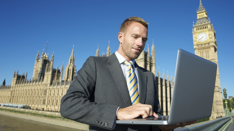 Man uses laptop on Parliament Bridge outside Westminster