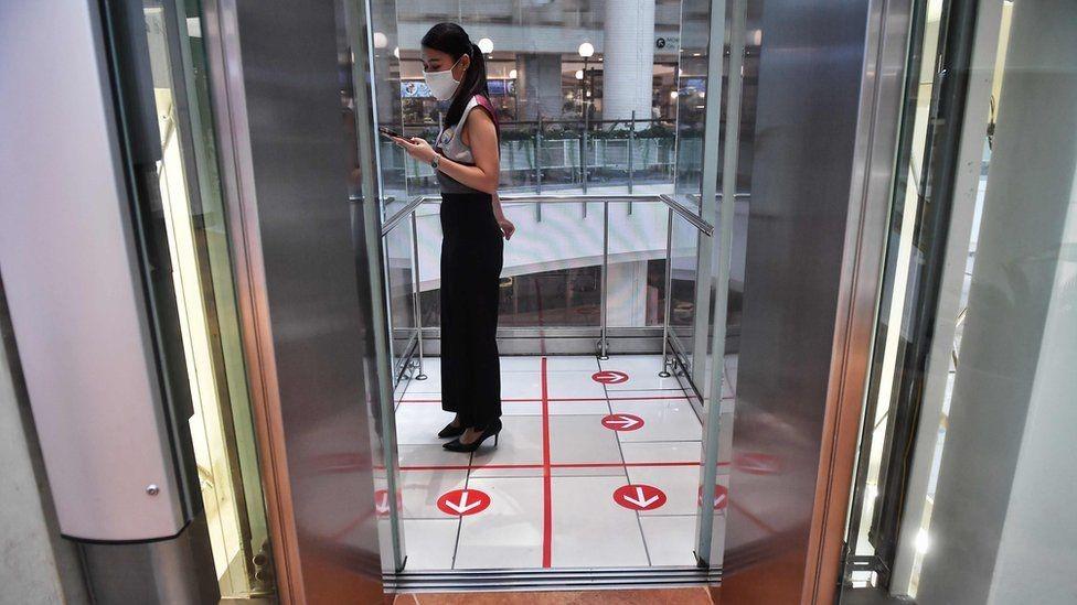 Una mujer asiática en un ascensor