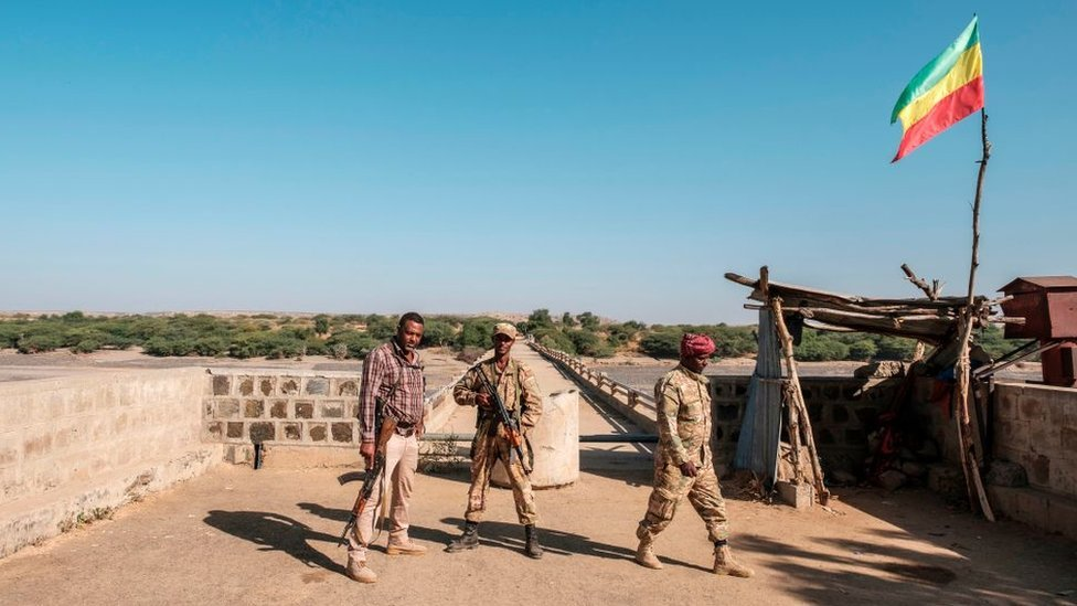 Two members of the Amhara Special Forces with a member of the Amhara militia (L) stand at the border crossing with Eritrea where an Imperial Ethiopian flag waves, in Humera, Ethiopia, on November 22, 2020.