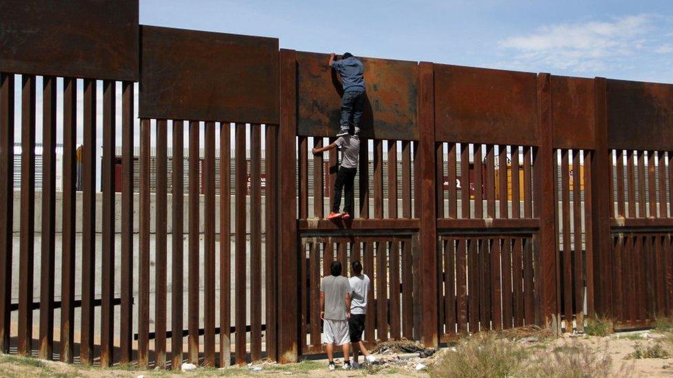 Una personas saltan el muro fronterizo entre Estados Unidos y México.