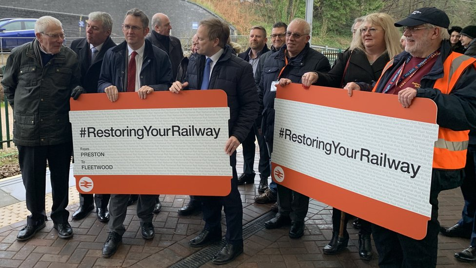 Grant Shapps and people holding giant rail tickets on the platform at Fleetwood