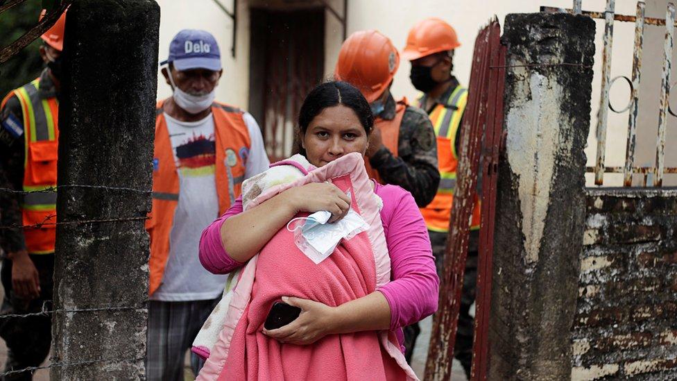 Una mujer con un bebé en brazos desaloja su casa en Honduras acompañada del ejército