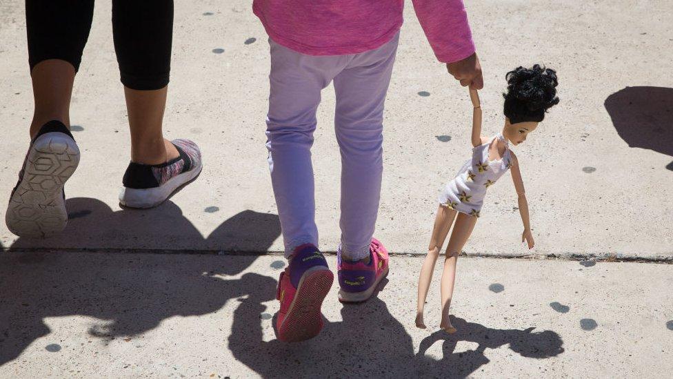 Una niña camina junto a una adulta.