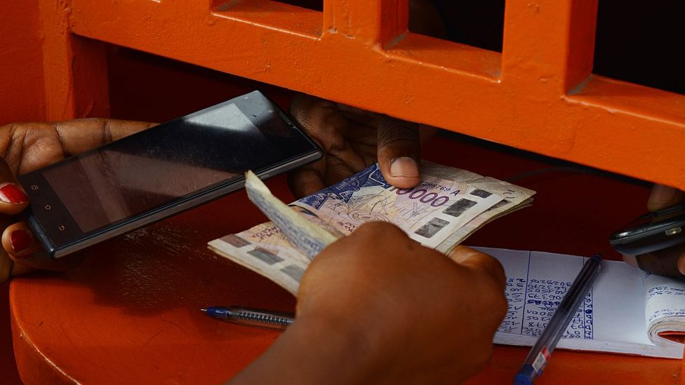 A woman withdraws money at an Orange Money cashier booth