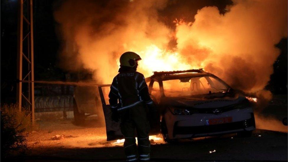 Un bombero israelí cerca de un vehículo policial incendiado el 12 de mayo de 2021.