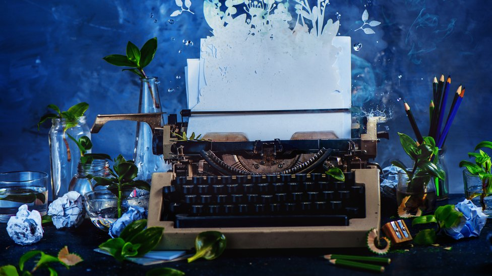 Creative picture of a typewriter surrounded by flowers