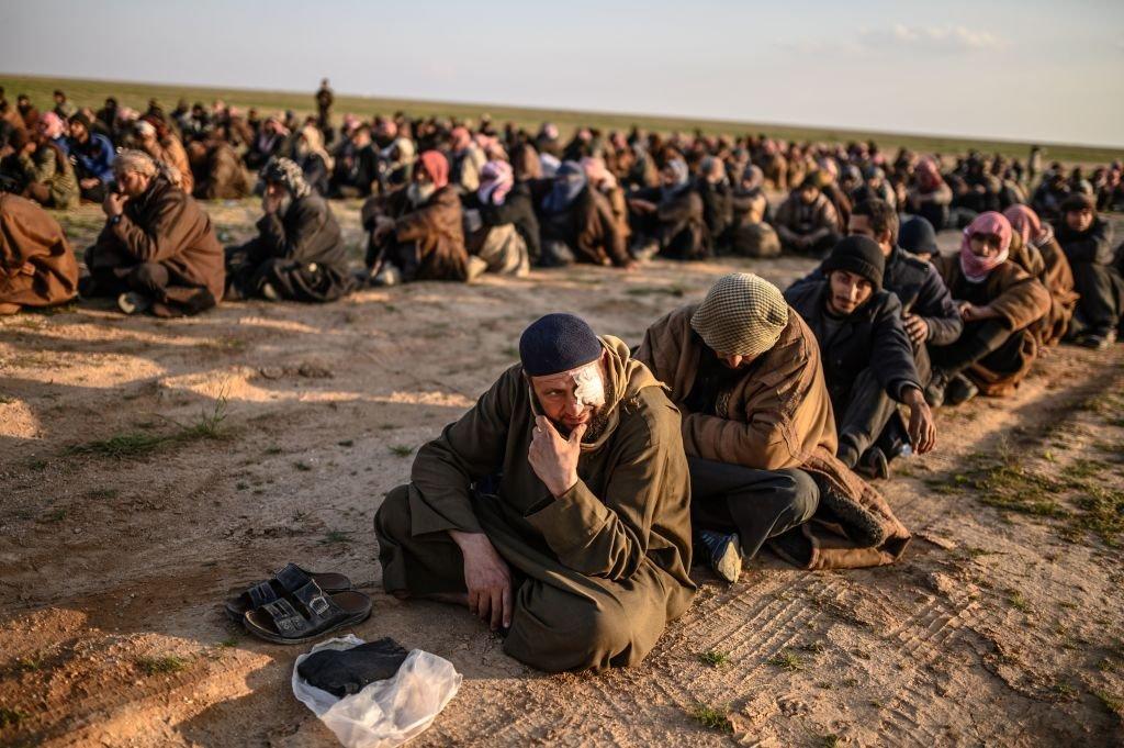رجال يشتبه بهم أن يكونوا من مقاتلي تنظيم الدولة الإسلامية، ينتظرون أن يتم تفتيشهم من قبل مقاتلي قوات سوريا الديمقراطية التي يقودها الأكراد بعد مغادرة آخر معاقل تنظيم الدولة الإسلامية في الباغوز ، في محافظة دير الزور شمالي سوريا ، 22 فبراير/شباط 2019.