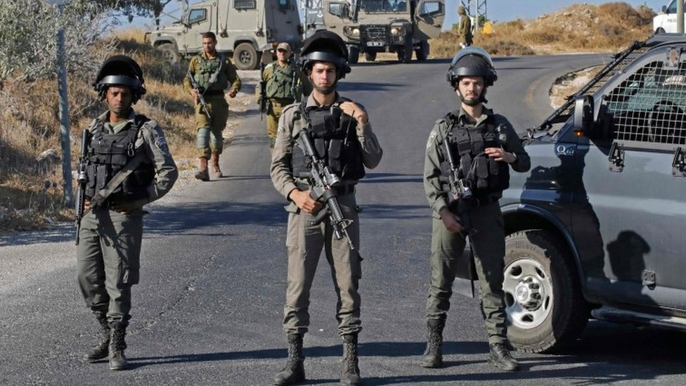Israeli soldiers stand guard next to the site where the body of an Israeli soldier was found