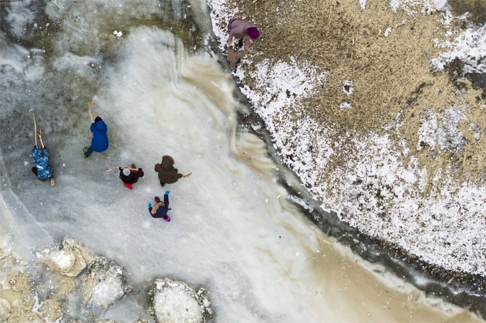A picture taken with a drone shows children playing ice hockey with wood sticks on an icy patch by the frozen shore of the Lake of Neuchatel, in Yverdon-les-Bains, Switzerland, 28 February 2018