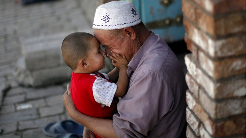 A Uighur man plays with a child in Kashgar, Xinjiang, China (file image)