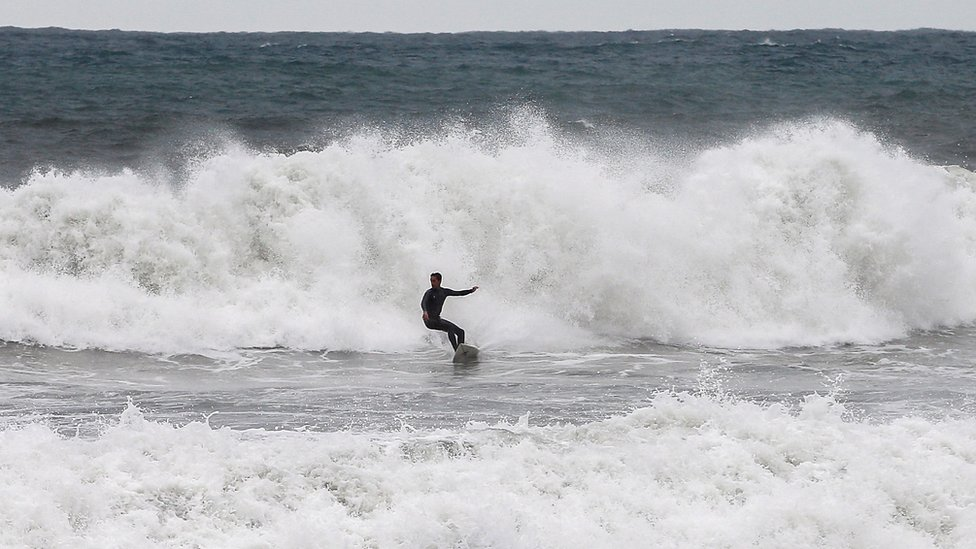 A surfer takes advantage of the big waves breaking at Barceloneta beach in Barcelona, Spain