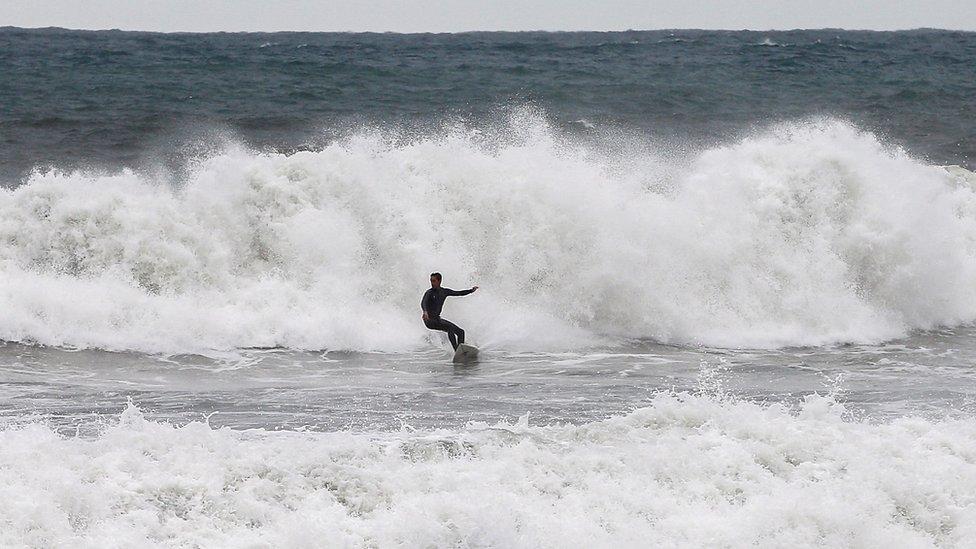 Серфер пользуется преимуществами больших волн, разбивающихся на пляже Барселонета в Барселоне, Испания.